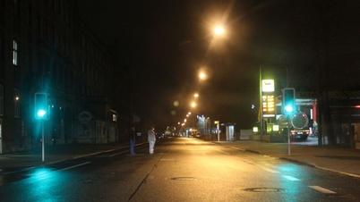 Dunkle Straße mit Fußgängern