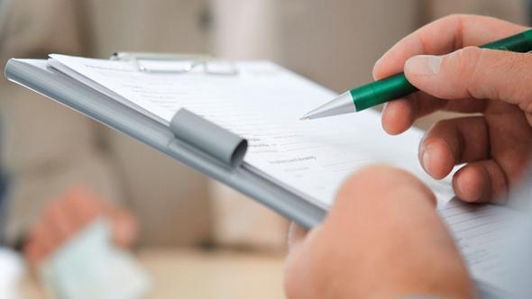 Mann mit Fragebogen und Kugelschreiber in der Hand