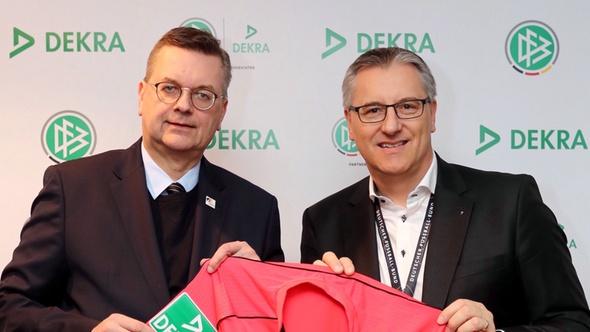 DFB-Präsident Reinhard Grindel (links) und DEKRA Vorstandschef Stefan Kölbl freuen sich über den neuen Vertrag. Beide Personen halten gemeinsam ein Schiedsrichtertrikot.