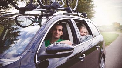 Eine Familie fährt in einem Auto mit einem Fahrraddachträger, beladen mit E-Bikes.