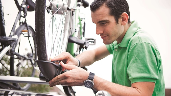 Fahrräder sicher transportieren: Mann befestigt Träger und Rad am Auto