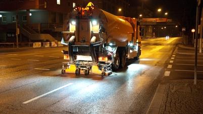 Straßenreinigungsfahrzeug fährt bei Nacht durch Stuttgart
