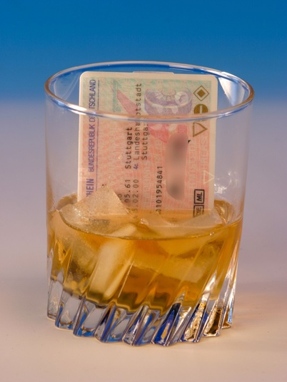 Whisky Glas mit Eiswürfel, Whisky und Führerschein darin
