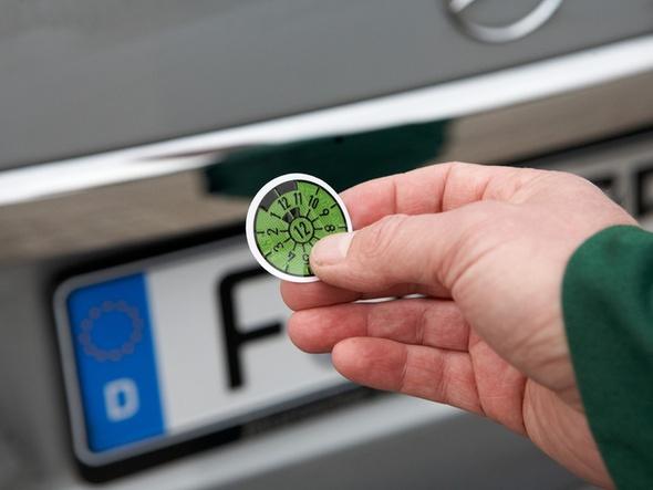 Hand mit Fahrzeugplakette