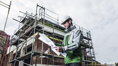 DEKRA Experte studiert einen Plan vor einem Baugerüst