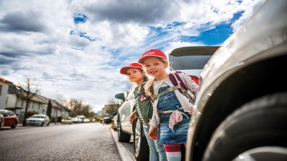 Zwei Schulkinder mit DEKRA Kappen schauen am Straßenrand zwischen den Autos hervor.