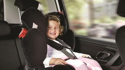 Ein Mädchen im Auto im Kindersitz sitzend
