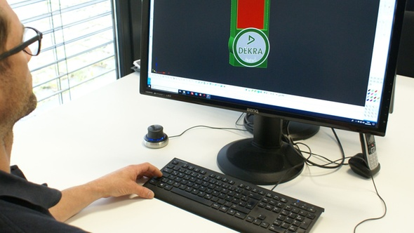 Mann am PC sitzend, schaut auf seinen Bildschirm