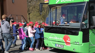 Kinder mit roten DEKRA Kappen steigen in den grünen DEKRA Bus