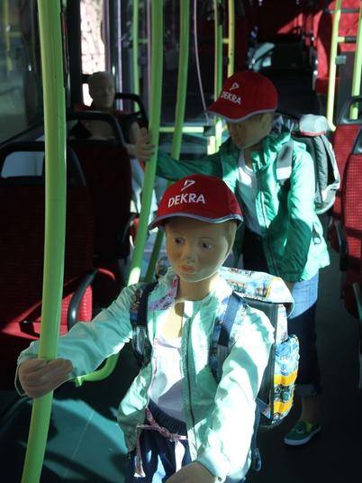 Kinder Dummys mit roten DEKRA Kappen im DEKRA BUS