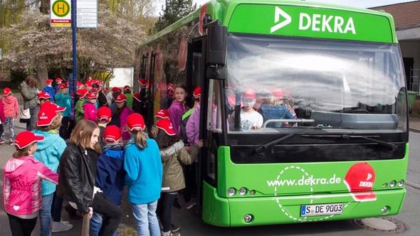 Kinder mit roten DEKRA Kappen vor und im grünen DEKRA Bus an einer Haltestelle
