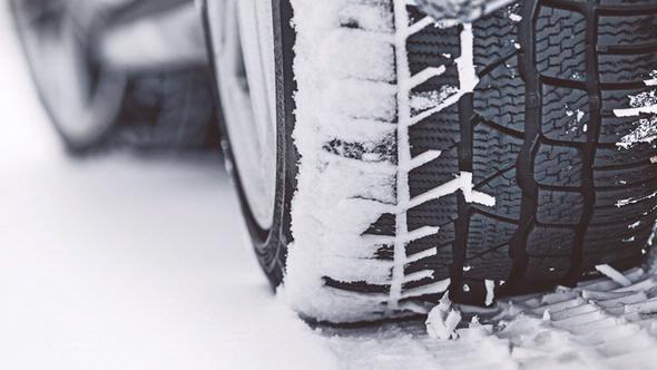 Großaufnahme Winterreifen die über eine Schnee fahren